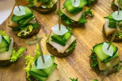 Canape with salted lard, onion, cucumber, rye bread and parsley. Catering banquet table with different food snacks. Appetizers Stock Image