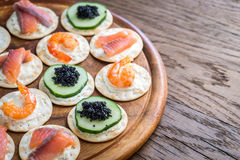 Canape with seafood on the wooden board Stock Photos
