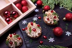 Canape shaped as a Christmas tree with pate garnished with pomegranate and dill. Surrounded by Christmas decorations royalty free stock images