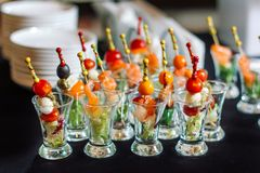 Canape with shrimps and salmon. Canape with shrimps and salmon on a table covered with a black cloth royalty free stock image