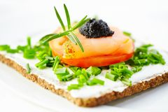 Canape with smoked salmon, soft cheese, tomato and caviar. stock images