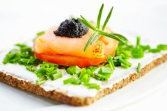 Canape with smoked salmon, soft cheese, tomato and caviar. royalty free stock photography