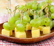 Canape snack - cheese with green grapes Stock Photos