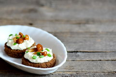 Canape with soft cheese and mushrooms on a plate on a wooden background with copy space for text Royalty Free Stock Photos