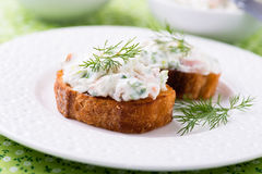 Canape with soft cheese spread on white plate Stock Photos