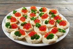 Canapees met boter, rode kaviaar en peterselie wordt behandeld die stock afbeelding