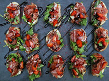 Canapes with bacon, strawberries and greens, poured a  shiny br Stock Photography