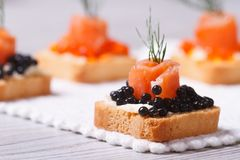 Canapes with black caviar, salmon and dill. macro. Royalty Free Stock Image