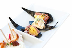 Canapes on black plastic spoons on ceramic tray Stock Images