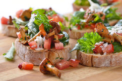 Canapes with chanterelles. Delicious canapes with rucola-tomato-salad and fried chanterelles royalty free stock photography