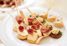 Canapes with cheese, ham and fruits Royalty Free Stock Image