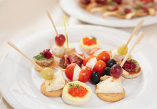 Canapes with cheese, ham and fruits Stock Images