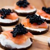 Canapes com salmões e caviar Fotografia de Stock Royalty Free