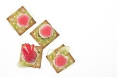 Canapes con l'uva, la fragola, la gelatina e la crema Fotografia Stock
