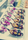 Canapes with cured ham on banquet table, toned photo Stock Image
