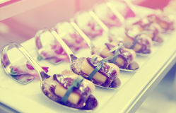 Canapes with cured ham on banquet table, toned photo Royalty Free Stock Image