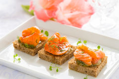Canapes délicieux d'apéritif de pain noir avec les saumons fumés images libres de droits