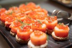 Canapes de color salmón rojos con el caviar rojo a bordo Cierre de los mariscos encima del tiro foto de archivo