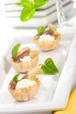 Canapes de la alcachofa, de la anchoa y del queso poner crema Fotografía de archivo