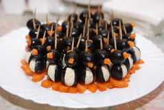 Canapes in the form of a penguin from olives. Carrots and cottage cheese Stock Image
