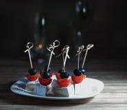 Canapes från camembert, körsbärsröda tomater och oliv på en mörk bakgrund Royaltyfri Fotografi