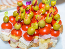 Canapes with ham tomato and olive on a toothpick Royalty Free Stock Photos