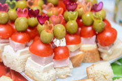 Canapes with ham tomato and olive on a toothpick Royalty Free Stock Images