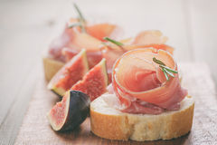 Canapes with jamon and figs on table Stock Photos