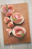 Canapes with jamon and figs on table Royalty Free Stock Images