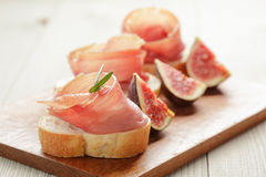 Canapes with jamon and figs on wooden board Stock Photography