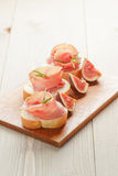 Canapes with jamon and figs on wooden board Royalty Free Stock Images