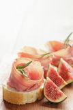 Canapes with jamon and figs on wooden board Royalty Free Stock Photo