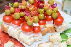Canapes mit Schinkentomate und -olive auf einem Zahnstocher Stockfoto