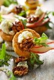 Canapes mit Zusatz des Blauschimmelkäses, der frischen Birne, des Honigs, der karamellisierten Walnüsse und des Arugula Stockfotos