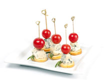 Canapes on a plate with cheese and cherry tomatoes Stock Images