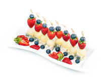 Canapes on a plate with cheese melon and strawberries Royalty Free Stock Images