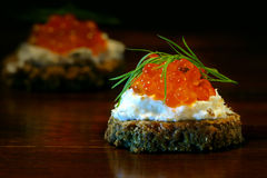 Canapes with red caviar with dill garnish on dark brown wood Stock Images