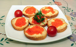 Canapes with red caviar on white plate Stock Images