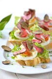 Canapes with roast beef and truffles royalty free stock photography