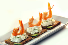 Canapes rye bread with ricotta cheese and tails of shrimps Stock Photography