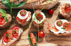 Canapes with salmon and cheese. Close up of bread with slamon, tomatos and cheese Stock Image