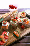 Canapes with salmon and cheese. Close up of bread with slamon, tomatos and cheese Royalty Free Stock Images