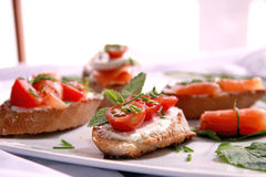 Canapes with salmon and cheese. Close up of bread with slamon, tomatos and cheese Stock Photography