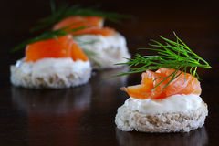 Canapes with salmon, cream and dill garnish, on dark brown wood,. Canape with salmon, cream and dill garnish, some canapes blurred in the background, on dark royalty free stock image