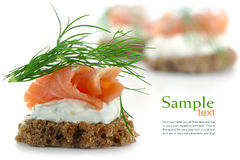 Canapes with salmon on cream and dill garnish, isolated on whit. Canape wiht salmon on cream and dill garnish, some canapes blurred in the background, isolated Royalty Free Stock Photos