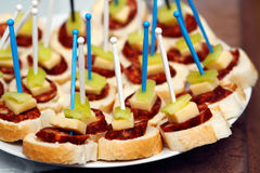 Canapes with sausage. Detail canapes with sausage, chees and pepper with plastic Toothpick Royalty Free Stock Photos