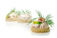 Canapes with shrimp cocktail, avocado and  dill garnish, isolate. Canape with north sea shrimp cocktail, avocado and fresh dill garnish, some canapes blurred in Stock Photos