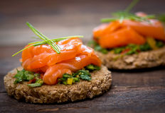 Canapes with smoked salmon. Herbs and spices on the table Royalty Free Stock Photography