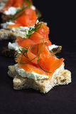 Canapes in star shape with smoked salmon on dark brown wood, fo Royalty Free Stock Photos