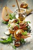 Canapes z błękitnym serem, świeża bonkreta, miód, karmelizowali orzechy włoskich i arugula Obrazy Stock